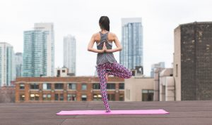 A woman doing yoga on a roof