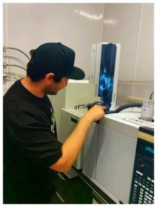 Chief Science Officer (CSO) Kevin Koby preparing the liquid injection autosampler to measure the volatile compounds in a cannabis extract.
